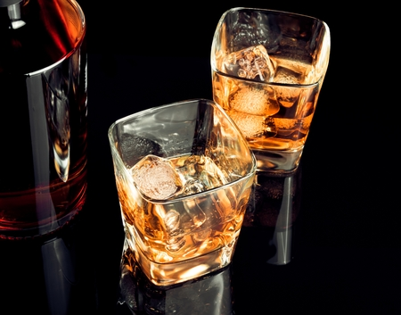 intoxicant: top of view of whiskey with ice in glass on black background, with reflection