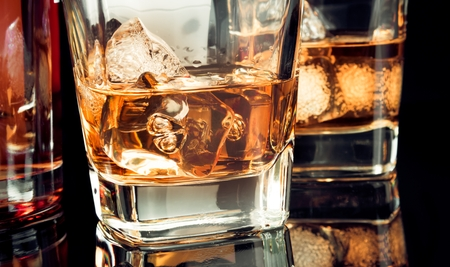 intoxicant: whiskey with ice in glass on black background near bottle, with reflection