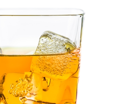 intoxicant: whiskey in glass with ice on white background, with space for text Stock Photo