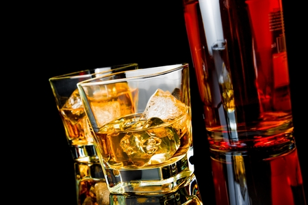 intoxicant: two whiskey with ice in glasses near bottle on black background, with reflection