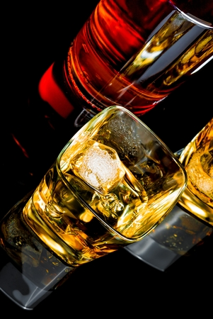 intoxicant: top of view of whiskey with ice in two glasses on black background, with reflection Stock Photo
