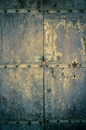 aged dark vintage wooden door as background with cuttings and scratch photo