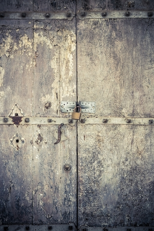 cuttings: aged dark vintage wooden door as background with cuttings and scratch