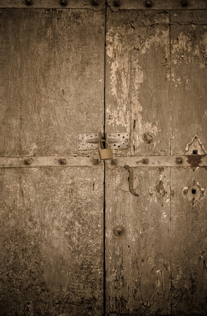 cuttings: aged dark vintage wooden door as background with cuttings and scratch and gold reflex