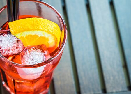 spritz: Top of view of spritz aperitif aperol cocktail with two orange slices and ice cubes on wood table