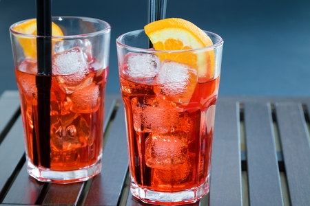 Spritz aperitif aperol cocktail with two orange slices and ice cubes on wood table Stock Photo