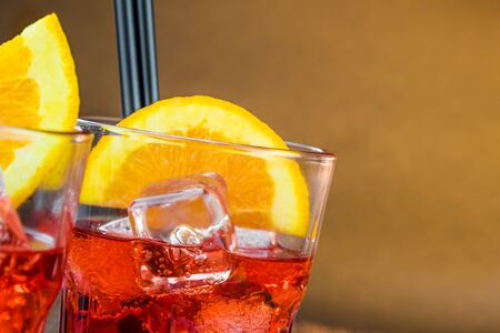 spritz: spritz aperitif aperol cocktail with orange slices and ice cubes on warm atmosphere with space for text
