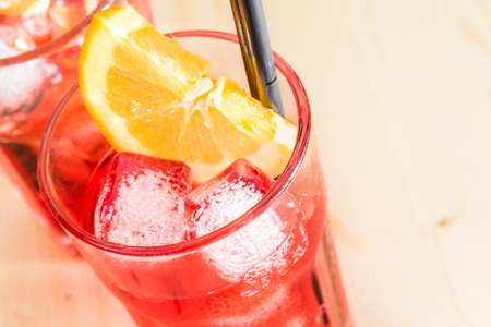 spritz: close-up of glass of spritz aperitif aperol cocktail with orange slices and ice cubes on wood table with space for text