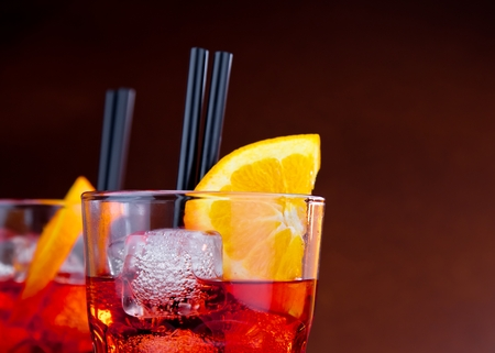 spritz: glasses of spritz aperitif aperol cocktail with orange slices and ice cubes oranges on wood table with space for text