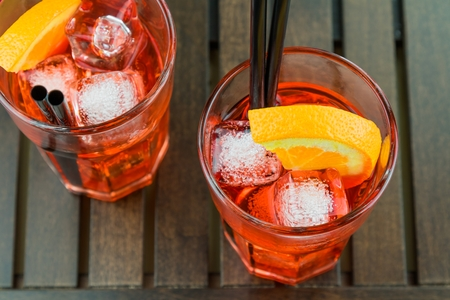 spritz: top of view of glasses of spritz aperitif aperol red cocktail with orange slices and ice cubes on wood table