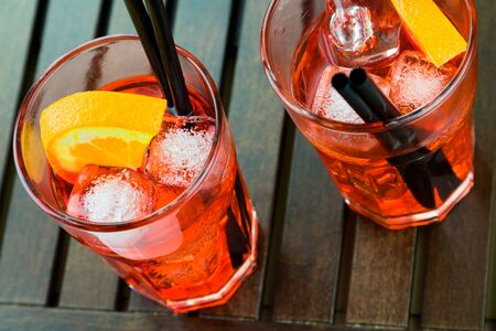 spritz aperitif aperol cocktail with orange slices and ice cubes on wood table Stock Photo
