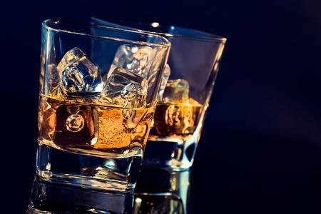whisky: deux verres de whisky avec des cubes de glace sur fond noir avec le bleu de la teinte de lumière et de réflexion, le temps de se détendre avec le whisky Banque d'images
