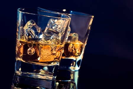 botella de whisky: dos vasos de whisky con cubitos de hielo sobre fondo negro con tinte azul luz y la reflexión, el tiempo de relajarse con el whisky