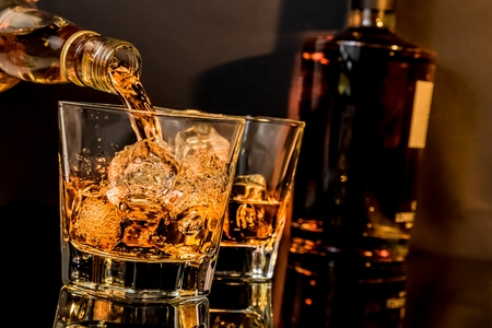 barman pouring whiskey in front of whiskey glass and bottles on black table with reflection