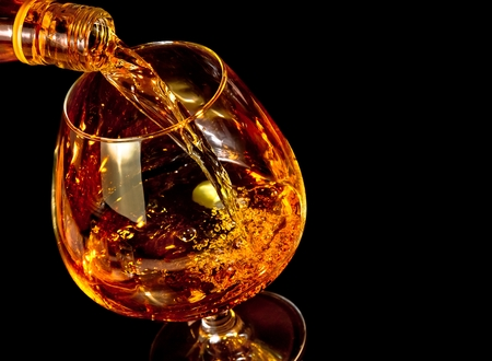barman pouring snifter of brandy in elegant typical cognac glass on black background with space for text Reklamní fotografie