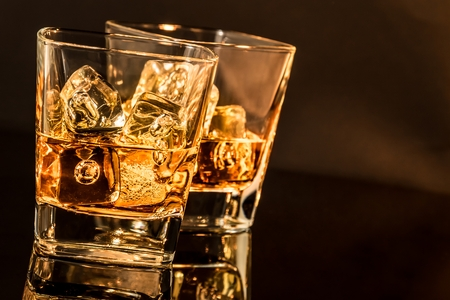 two glasses of whiskey on black table with reflection, warm atmosphere time of relax with whisky