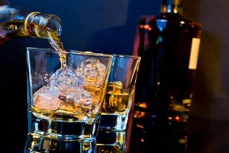 barman pouring whiskey in two glasses with ice cubes on table with light tint blue and reflection, time of relax with whisky
