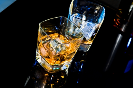 liquor glass: top of view of glass of whiskey near bottle on black table with reflection, time of relax with whisky Stock Photo