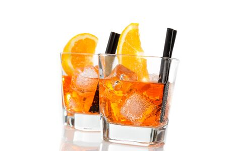 two glasses of spritz aperitif aperol cocktail with orange slices and ice cubes isolated on white background Stock Photo