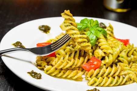 pasta: dish of pasta with pesto genovese sauce and vegetables, tomato and basil, detail of fork with fusilli on top on black wood table
