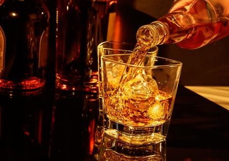 ウイスキー グラスと黒いテーブルの上の瓶の前にウィスキーを注いでバーマン