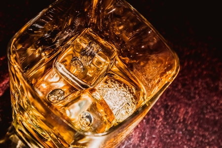 ices: top of view of glass of whiskey on wood table with focus on ices, warm atmosphere, time of relax with whisky with space for text