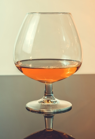 snifter of brandy in elegant typical cognac glass on light background, with reflection