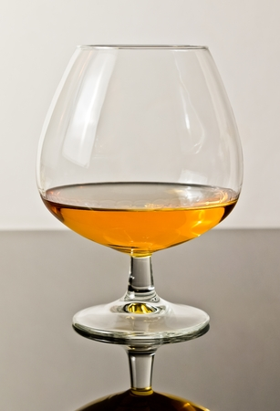 snifter of brandy in elegant typical cognac glass on white light background, with reflection Stock Photo