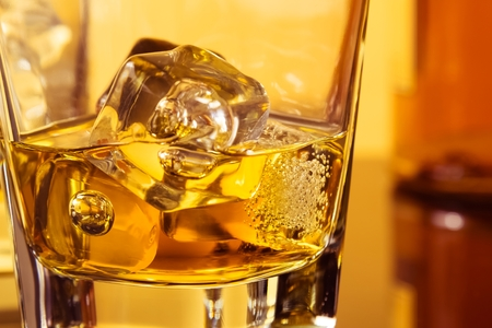 ices: detail of glass of whiskey with ices near bottle on table with reflection, warm atmosphere, time of relax with whisky