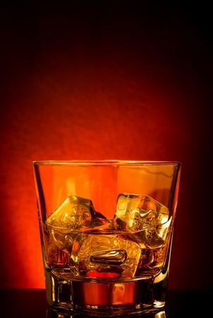 botella de whisky: vaso de whisky en la mesa negro con la reflexión, la atmósfera tinte rojo, el tiempo de relajarse con el whisky