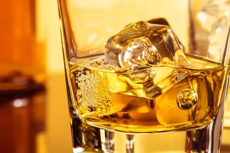 botella de licor: detalle de vaso de whisky con hielos cerca de la botella en la mesa con la reflexi�n, ambiente c�lido, el tiempo de relajarse con el whisky Foto de archivo