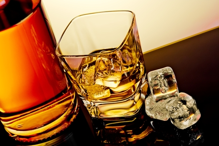 top of view of glass of whiskey near bottle and ice cubes on table with reflection, time of relax with whisky