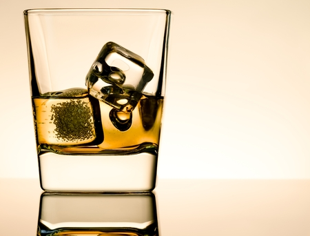 whisky glass: one glass of whiskey with ice cubes on table with reflection, light brown atmosphere, time of relax with whisky Stock Photo