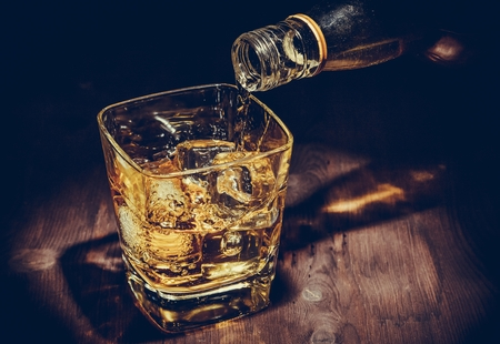 barman pouring whiskey in the glass on wood table, warm atmosphere, old style, time of relax with whisky