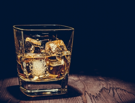 whiskey glass: glass of whiskey with ice cubes on wood table, warm atmosphere, time of relax with whisky with space for text