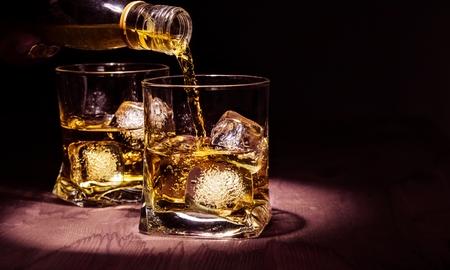 バーマン注ぐウィスキーの時間古いスタイル、温かみのある雰囲気の木のテーブルにガラスのテキストのためのスペースとウイスキーとリラックス