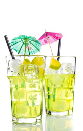 cocktail umbrella: two glasses with cocktail and ice with lime slice and cocktail umbrella on white background, disco summer concept Stock Photo