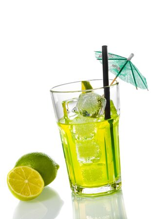 cocktail umbrella: glass with cocktail and ice near lime slice and cocktail umbrella on white background, disco summer concept Stock Photo