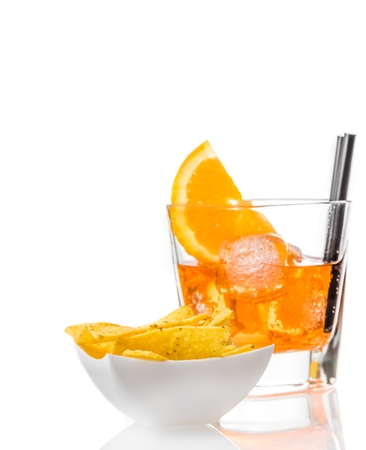 spritz: hot tacos chips in front of glass of spritz aperitif aperol cocktail with orange slices and ice cubes on white background