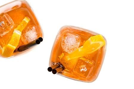 Anfang der Blick auf zwei Gläser Aperitif Spritz Aperol-Cocktail mit Orangenscheiben und Eiswürfeln auf weißem Hintergrund Standard-Bild - 47211391