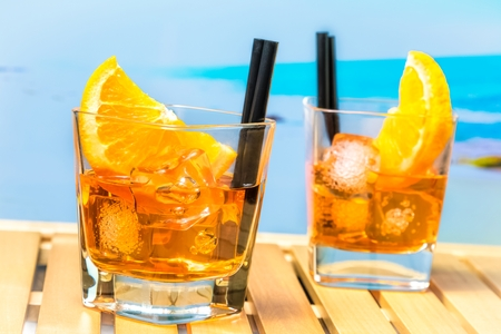 spritz: two glasses of spritz aperitif aperol cocktail with orange slices and ice cubes on blur beach background, summer concept Stock Photo