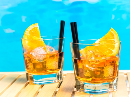 spritz: two glasses of spritz aperitif aperol cocktail with orange slices and ice cubes on swimming pool background, summer concept