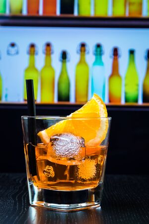 lounge bar: glass of spritz aperitif aperol cocktail with orange slices and ice cubes on bar table, disco lounge bar atmosphere background, lounge bar concept