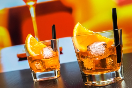 lounge bar: two glasses of spritz aperitif aperol cocktail with orange slices and ice cubes on bar table, disco atmosphere background, lounge bar concept Stock Photo