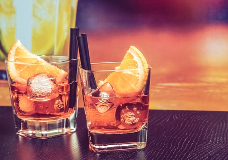 glasses of spritz aperitif aperol cocktail with orange slices and ice cubes on bar table, vintage atmosphere background, lounge bar concept