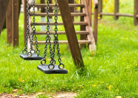 playground equipment: empty swings at playground for child, on green meadow background