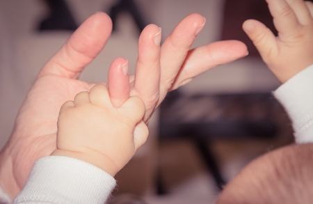 love image: newborn baby hand playing with adult finger, maternity concept, love image beautiful family