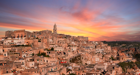 sassi: panoramic view of typical stones and church of Matera under sunset sky. Basilicata, Italy