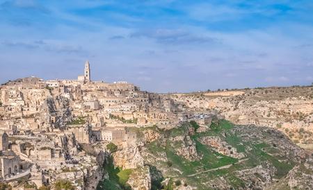 sassi: panoramic view of typical stones (Sassi di Matera) and church near gravina of Matera UNESCO European Capital of Culture 2019 on blue sky. Basilicata, Italy