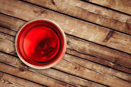 top of view of red wine in the glass isolated on wood background with space for text